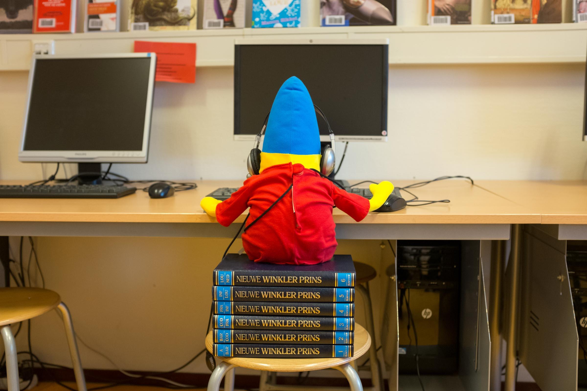 Foto van mascotte pompom achter een computer
